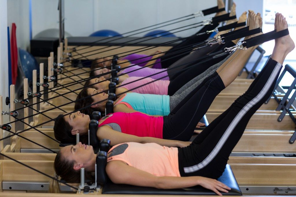 Group of women using pilates reformer