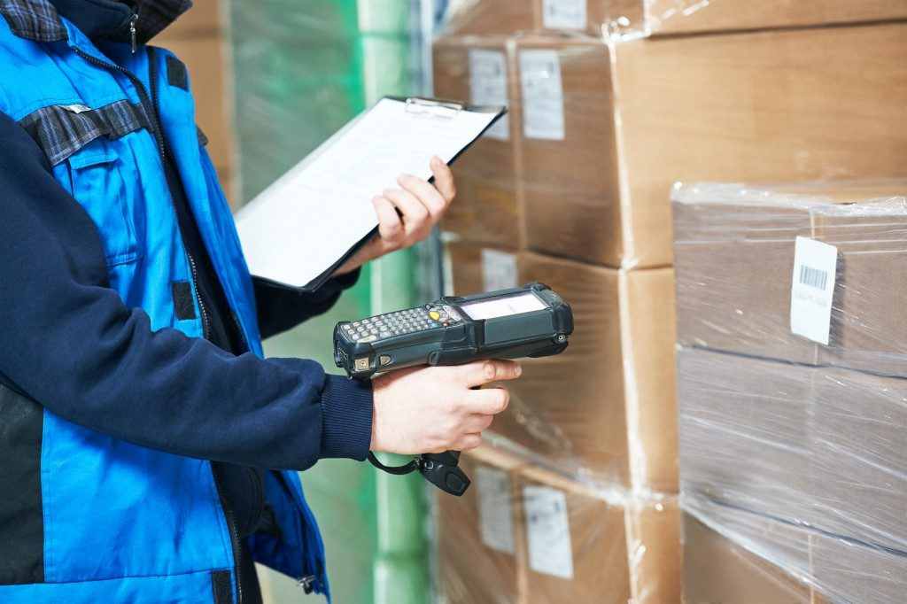 delivery man scanning barcodes of packages